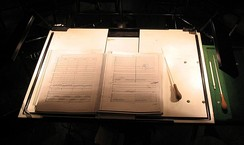 Conductor's score and batons on a lit, extra-large conductor's music stand