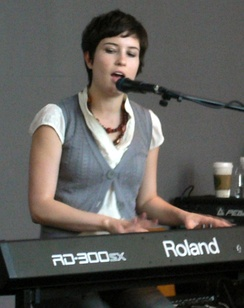 Higgins is seated. She sings into a microphone and plays a keyboard instrument. The lettering RD-300SX and Roland are visible across its front.