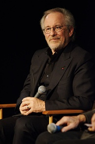 Steven Spielberg sits on a chair with a microphone in his hand