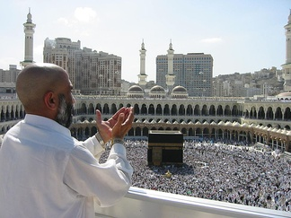 A man raising his hands in prayer in front of the Kaaba