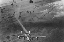 A USAAF B-24 bomber emerges from a cloud of flak with its no. 2 engine smoking.