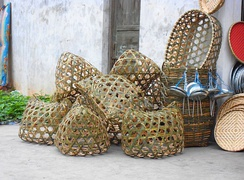 On the left side are live fowl baskets. Directly to the right are flat baskets used for selling shrimp and small fish in Haikou City, Hainan Province, People's Republic of China