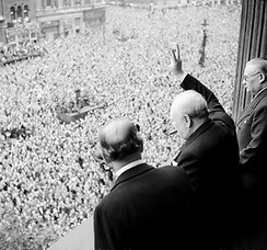 Churchill waving the Victory sign to the crowd in Whitehall on the day he broadcast to the nation that the war with Germany had been won, 8 May 1945. Ernest Bevin stands to his right.