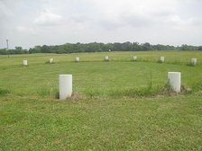 Barrels outline circular structures in the 37.5-acre (17.4 ha) plaza at Poverty Point
