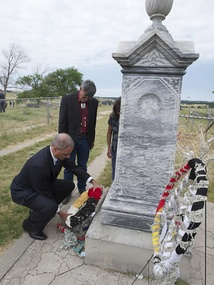 Holder laying a wreath at the memorial site of the Wounded Knee Massacre in South Dakota