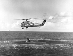 HUS-1 helicopter attempting to recover the Liberty Bell 7 capsule. The recovery ship USS Randolph is visible in the distance.