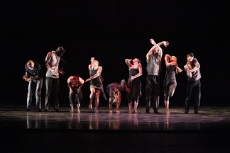 Members of an American jazz dance company perform a formal group routine in a concert dance setting