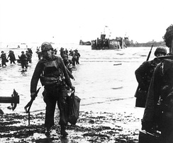 Carrying their equipment, US assault troops move onto Utah Beach. Landing craft can be seen in the background.