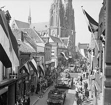 People in Eindhoven watching the allied forces enter the city following its liberation, similar to the depiction of the liberation in Black Book