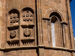 Flat striated pillars (one of which forms the axis of symmetry, separating two windows with semi-circular arches) and richly decorated blind windows in the apse of San Juan de Rabanera Church in Soria, Spain.