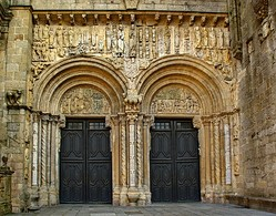 The Porta Platerias, Cathedral of Santiago de Compostela, by Master Esteban, has two wide openings with tympanums supported on brackets. The sculptured frieze above is protected by an eave on corbels.