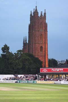 Cricket ground in front of a church tower.