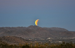 A full moon appears as a half moon during an eclipse moonset over the High Desert in California, on the morning of the Trifecta: Full moon, Supermoon, Lunar eclipse, January 2018 lunar eclipse