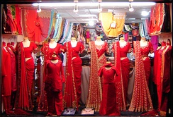 Display of traditional sarees with gota patti embroidery for festive occasions at clothing store.