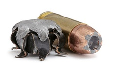 Right: .40 S&W round with hollow-point bullet, Left: expanded bullet of the same calibre with exposed lead core