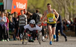 A runner gives a friendly tap on the shoulder to a wheelchair racer during the Marathon International de Paris (Paris Marathon) in 2014.
