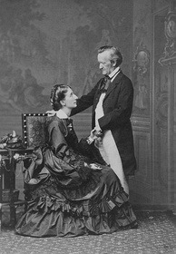 A couple is shown: On the left is a tall woman of about 30. She wears a voluminous dress and is sitting sideways in an upright chair, facing and looking up into the eyes of the man who is on the right. He is about 60, quite short, balding at the temples. He is dressed in a suit with tailcoat and wears a cravat. He faces and looks down at the woman. His hand rests on the back of the chair.