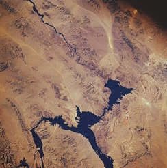 Lake Mead from space in November 1985: North is facing downward to the right. The Colorado River can be seen leading southward away from the lake on the top left. The Hoover Dam is located where the river meets the lake.