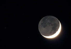 An overexposed photograph of a crescent Moon reveals earthshine and stars.