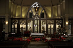 Midnight Mass is held in many churches toward the end of Christmas Eve, often with dim lighting and traditional decorative accents such as greenery