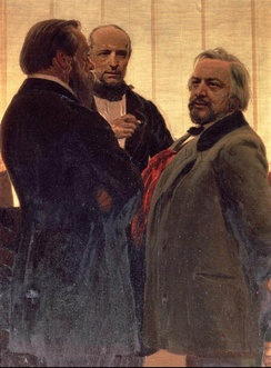 Three men standing together – two men with beards, the one on the right with grey hair, flanking a third man watching them intently