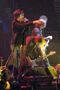Frontline of Powderfinger are shown in side profile across a stage, with Fanning closest to viewer. He is pointing into the audience with his right fore-finger, while singing into the microphone held in his left hand. Just beyond him, Collins is stooped low over his bass guitar with his long hair fallen forward. Haug is further along and plays his guitar while standing more upright, his shoulder length hair partly obscures his face. Stage equipment is in front of the three men.