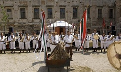 Gathering of a Hungarian Native Faith group for the performance of a ritual. The two leading figures hold ritual spears with strips of cloth of the colours of the flag of Hungary tied near the tips.