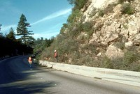 State Route 1 collapsed near Watsonville with Loma Prieta Peak visible in background (left) and landslide debris blocking both eastbound lanes of Highway 17 near Summit Road