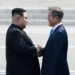 Moon and Kim shaking hands over the demarcation line on 27 April 2018