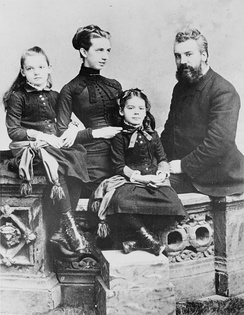 A distinguished bearded man, his young elegant wife next to him and their two young daughters poise for a formal portrait