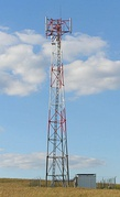 A BTS tower. The antenna is on top and the shelter housing the BTS on the right