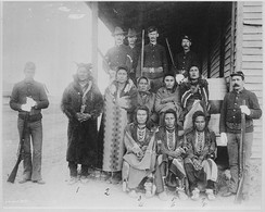 Chief Plenty Coups and seven Crow prisoners under guard at Crow agency. Montana, 1887
