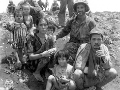 Sgt. Victor Maghakian in July 1944 with Japanese soldier's family found hiding in a cave and urged to come out by Chamorro guides with Marine units in Saipan.