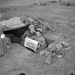 Men of the 2nd Royal Inniskilling Fusiliers reading Ireland's Saturday Night in their foxhole in the Anzio bridgehead, 17 March 1944