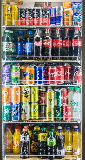 Soft drinks displayed on grocery store shelves.