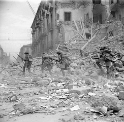 British troops scramble over rubble in a devastated street in Catania, Sicily, 5 August 1943.