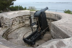 British 64 Pounder Rifled Muzzle-Loaded (RML) Gun on a Moncrieff disappearing mount, at Scaur Hill Fort, Bermuda. This is a part of a fixed battery, meant to protect against over-land attack and to serve as coastal artillery.