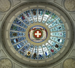 The 22 cantonal coats of arms (all but Jura, with the half-cantons represented jointly) in stained glass set in the dome of the Federal Palace of Switzerland (c. 1900)