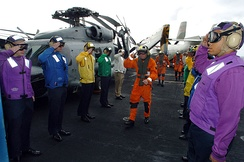 Flightdeck personnel on board an aircraft carrier wearing different colored jerseys, denoting a specific function. (U.S. Navy)