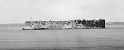 Fort Sumter, reduced to a shapeless pile of rubble, photographed by Haas & Peale across an active front (Note the Confederate flag flying above the parapet), soon after the evacuations of batteries Greg and Wagner on September 7, 1863