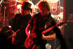 Two members from the band King Diamond are shown at a concert performance. From left to right are the singer and an electric guitarist. The singer has white and black face makeup and a top hat. Both are wearing black.