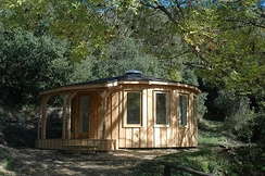 "A modern-day roundhouse - one of many constructed by a UK firm ""Rotunda Roundhouses"" [1] attempting to revive the ancient form of architecture and make it more compatible for contemporary living"