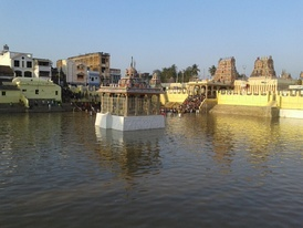 image of a temple tank with temple tower and complex in the background