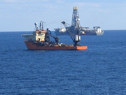 The drillship Discoverer Enterprise is shown in the background, at work during exploratory phase of a new offshore field. The Offshore Support Vessel Toisa Perseus is shown in the foreground, illustrating part of the complex logistics of offshore oil and gas exploration and production.