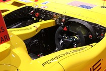 A view of the cockpit of a Porsche RS Spyder racing car showing the dashboard and steering wheel