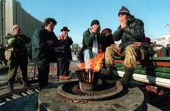 Чеченские террористы-«дудаевцы» молятся у Вечного огня напротив здания «Президентского дворца». Грозный, декабрь 1994. Фото М. Евстафьева