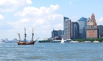 A replica of the VOC's Halve Maen (captained by Henry Hudson, an Englishman in the service of the Dutch Republic) passes modern-day lower Manhattan, where the original ship would have sailed while investigating New York harbor