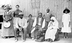 "Tubman in 1887 (far left), with her husband Davis (seated, with cane), their adopted daughter Gertie (beside Tubman), Lee Cheney, John ""Pop"" Alexander, Walter Green, Blind ""Aunty"" Sarah Parker, and great-niece, Dora Stewart at Tubman's home in Auburn, New York"