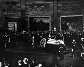 United States President Lyndon B. Johnson placing a wreath before the flag-draped casket of President Kennedy, during funeral services held in the United States Capitol Rotunda, November 24, 1963.