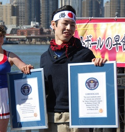 Japanese competitive eater Takeru Kobayashi with two Guinness World Record certificates